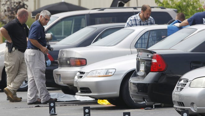 Police investigate the scene of a shooting that left three dead in the parking lot of Jordan Manufacturing in Monticello Tuesday, Aug. 5, 2014.