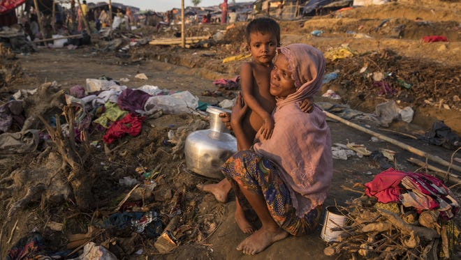 Rahima Begum, 25, holds her daughter Taslima, 4, as they wait to be relocated to another camp on Sept. 25, 2017, in Cox's Bazar, Bangladesh.