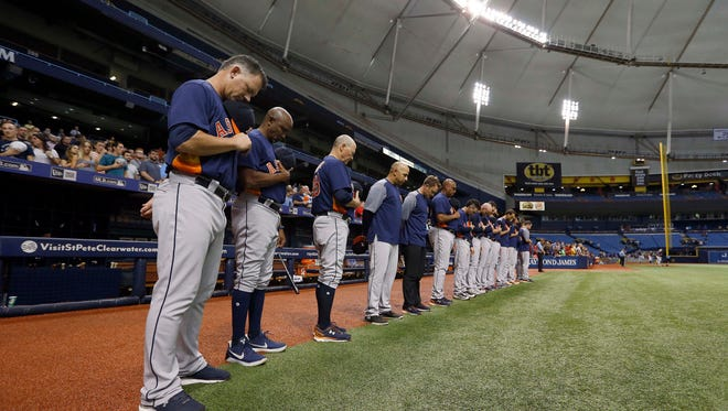 Astros manager A.J. Hinch and teammates stand for a moment of silence for those impacted by Hurricane Harvey at Tropicana Field.