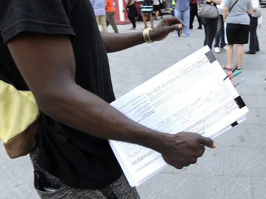 A petitioner gathers signatures in Campus Martius in downtown Detroit.