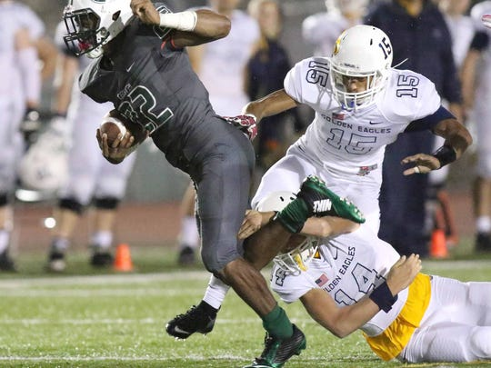 Miami Central running back Khori Roberts (22) attempts to escape  Naples defenders Terrell Posada (15) and Noah Biggs (14) during the Class 6A semifinal playoff football game on Friday, December 4,  2015 at Traz Powell Stadium in Miami