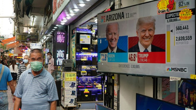 A man walks past a TV monitor showing a news program reporting the U.S. presidential election between President Donald Trump, right, and former Vice President Joe Biden, left, in Hong Kong, Wednesday, Nov. 4, 2020.