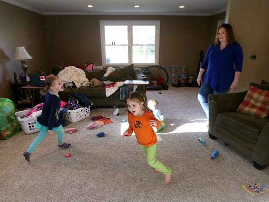Maggie Walker looks on as daughters Abby, 5, left,