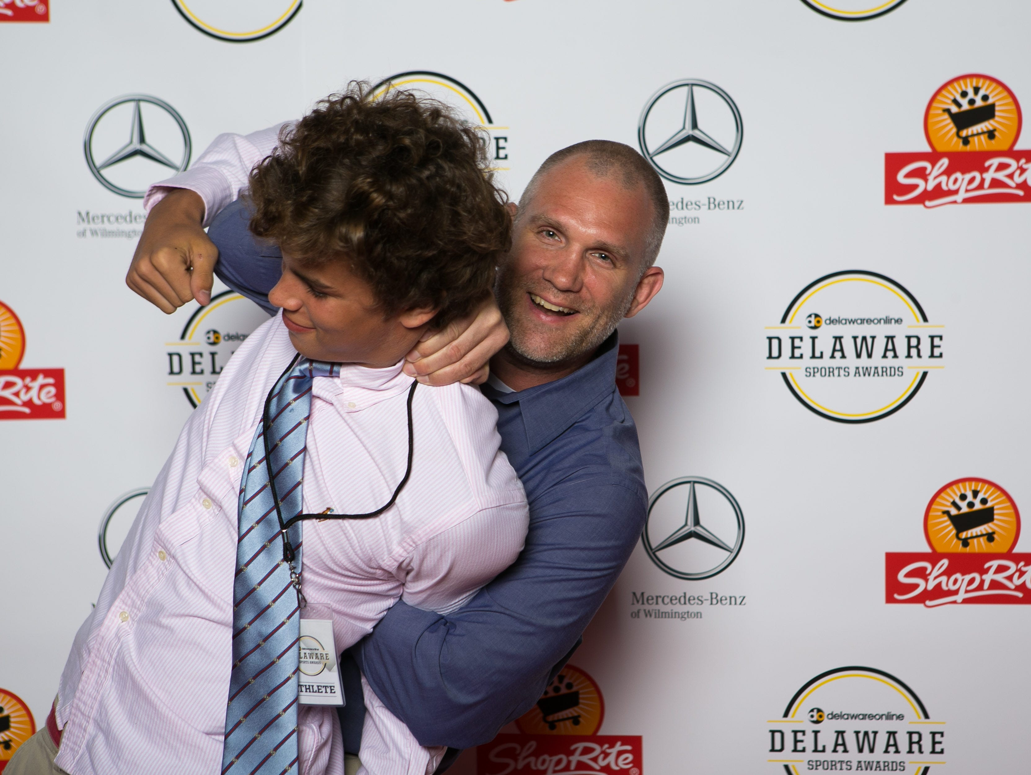 Coach Cory Frederick puts a wrestling move on Andrew Brooks on the red carpet at the Delaware Sports Awards.