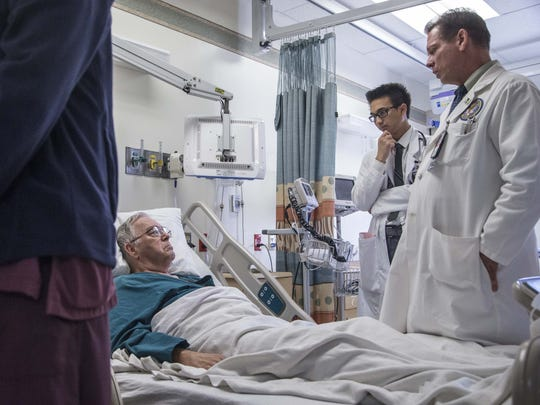 Dr. Michael Chesser (right), a hospitalist at the Phoenix VA Medical Center, diagnoses patient William Johnson.
