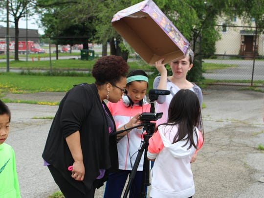 Even a little rain does not deter RCTV camp instructor Rashida Washington and students at the RCTV/Writers & Books camp from filming their submissions.