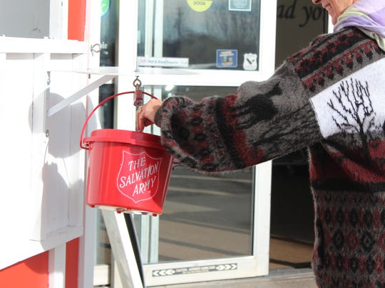A donor drops money inside the Salvation Army's red kettle.