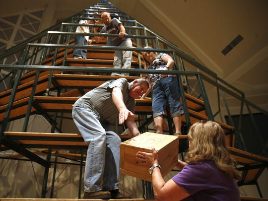 Jim Overall, center, works in the assembly line to get boxes up the singing Christmas tree at Bradfordville First Baptist Church Monday. The boxes are used to ensure the nearly 50 choir members are standing at equal heights while singing from the 45-foot-tall structure during a Christmas concert series at the church Dec. 11-13.