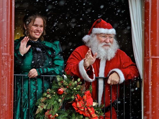 Santa Claus and a helper, Snowflake, wave from a car