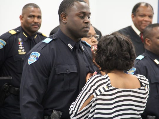 Officer Navarsea Conneris presented his badge during a pinning ceremony after graduating the police academy and accepting a position with Monroe Police Department.