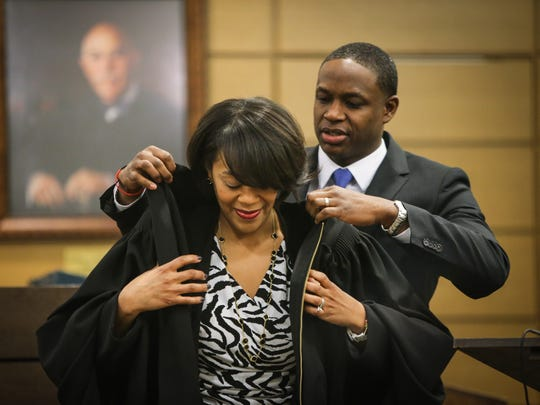 Judge Natalie Haskins puts on her robes for the first time with the assistance of her husband, Tarik Haskins, during an investiture ceremony at the New Castle County Courthouse Friday.