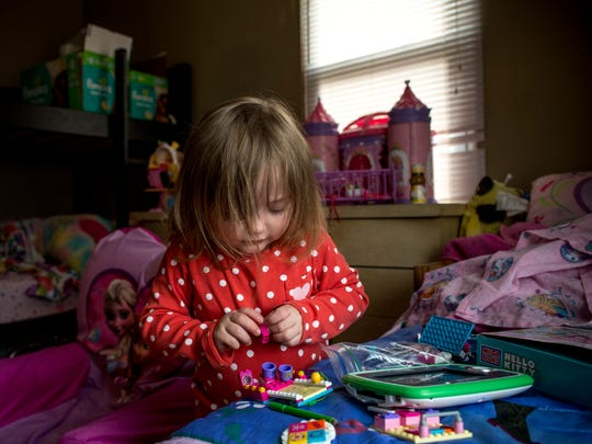 Makayla, 4, looks down as she concentrates putting together a Lego set on her bed Thursday, Feb. 4, 2016 at her home in Marysville.