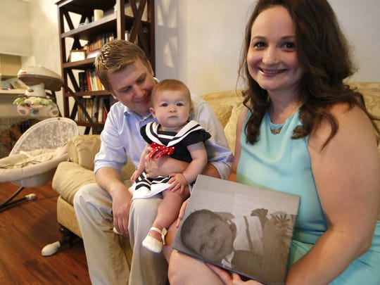 Steven and Rachel Tribble hold their 9-month-old daughter