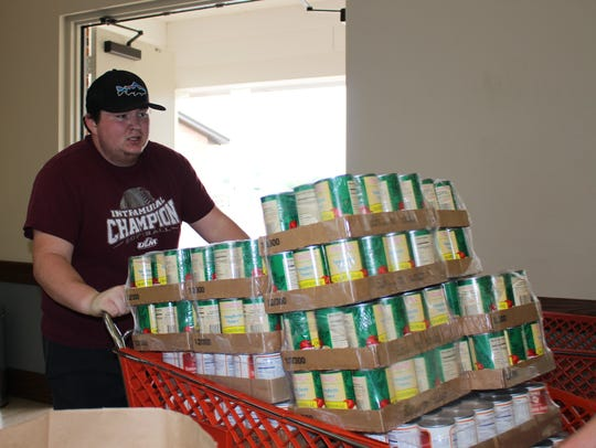 Jake Monnin pushes a cart of canned vegetables into