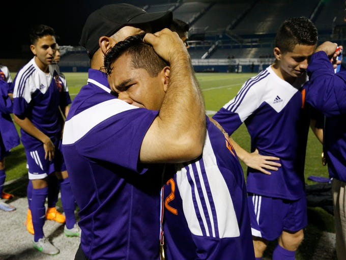 Eastlake head coach Gibby Widner comforts one of his