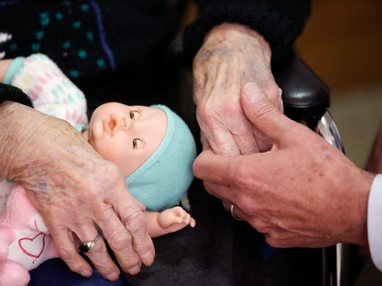 A son holds his mother's hand at her nursing home in