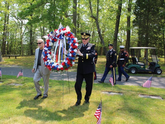 Dennis Levinson (left) and retired Brig. Gen. Jeffrey L. Pierson Sr. (right) walk the Memorial Wreath to the base of the flag pole in the center of the Atlantic County Veteran's Cemetery.