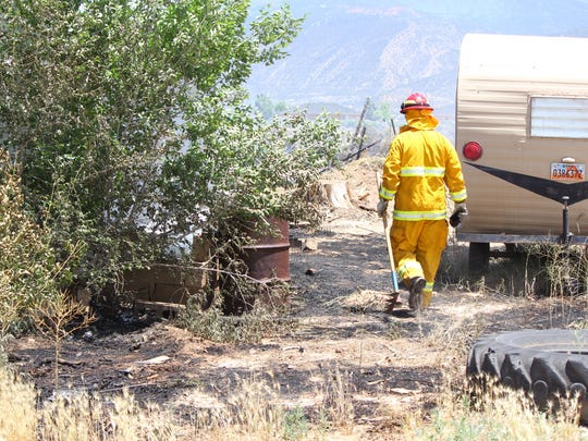 A firefighter checks for hot spots at a fire near two houses in Cedar City on Friday, June 10, 2016.