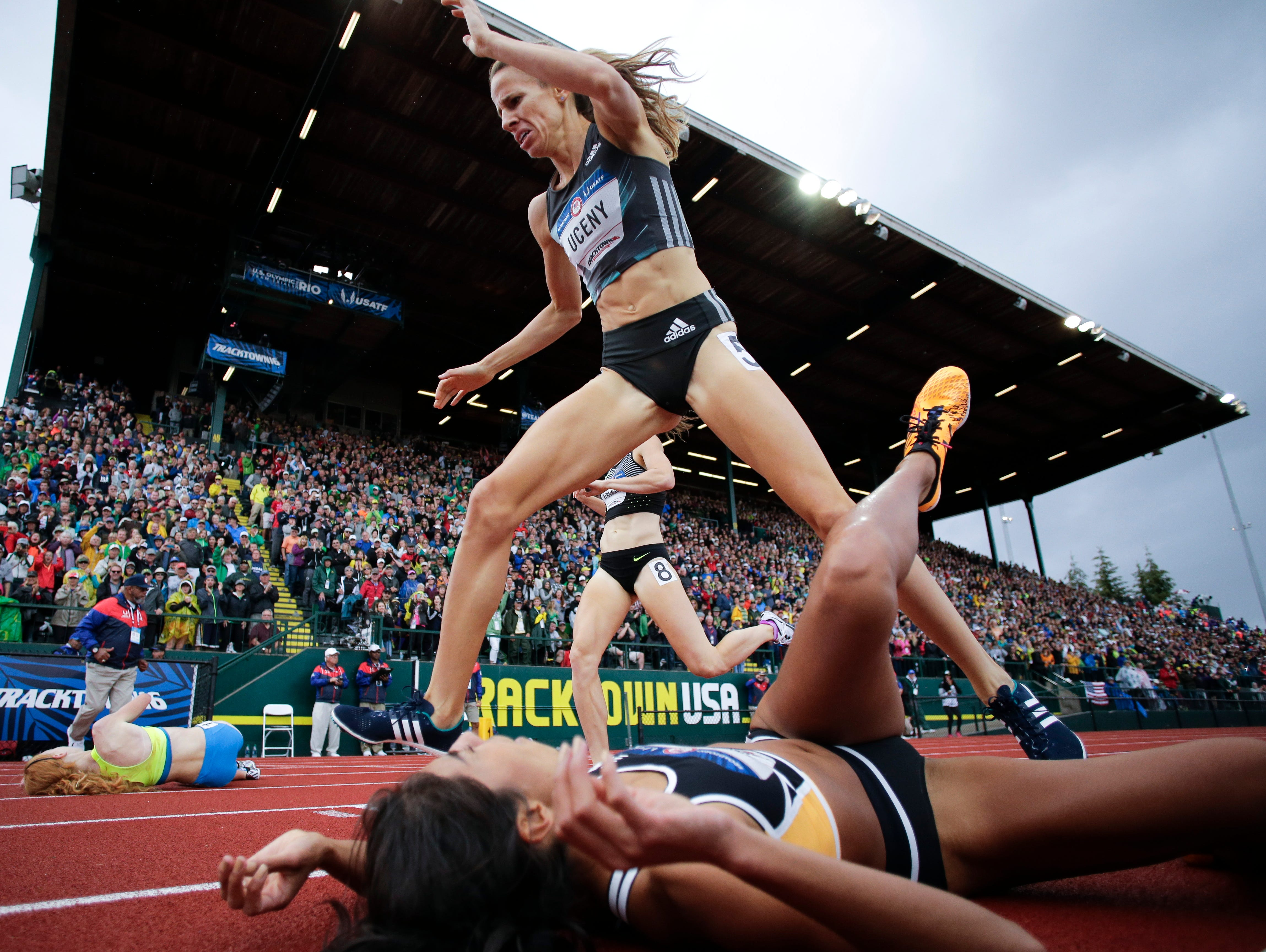 Morgan Uceny, top, steps over Brenda Martinez at the finish line in the finals of the women's 1500-meter run with at the U.S. Olympic Track and Field Trials, July 10, 2016, in Eugene Ore.