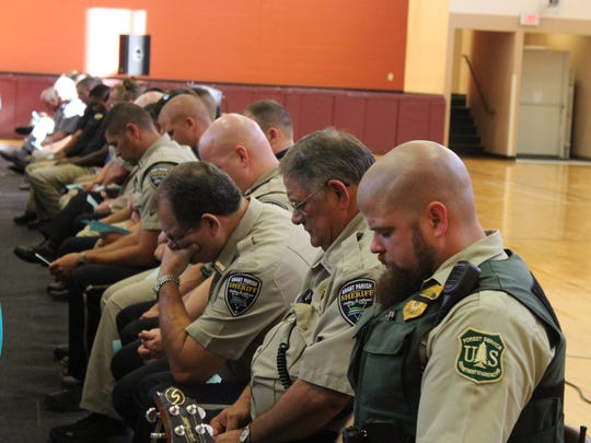 Grant Parish and U.S. Forest Service law enforcement members pray on Thursday during a service at Grant Junior High School.