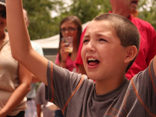 Julio Borbolla, 10, cheers as he swallows his last