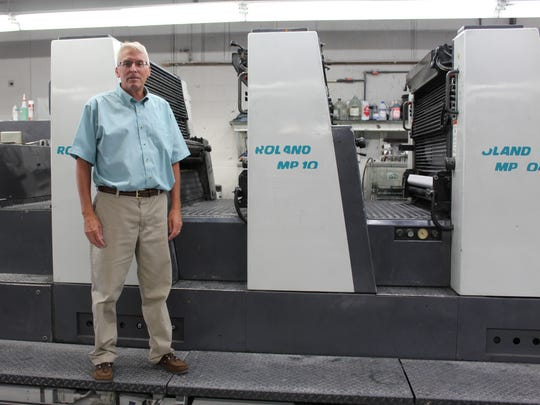 Alan Schillhammer, owner of Queen City Printers, is pictured in front one of five printing presses on Thursday.