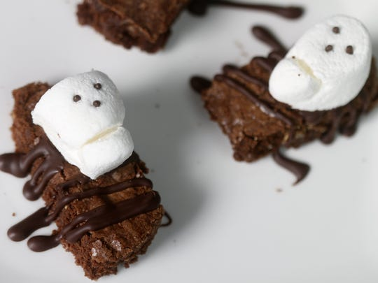 Chocolate sprinkles are used to create the eyes and nose of these Marshmallow Skulls on Brownie Coffins.
