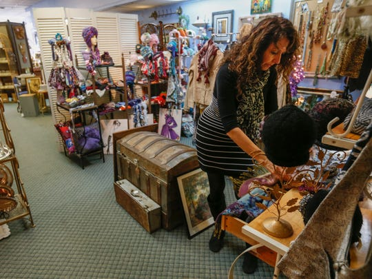 Valerie Richards sets up a display at A Cricket in the House, which is part of downtown's Small Business Saturday shopping open house on Thanksgiving weekend.