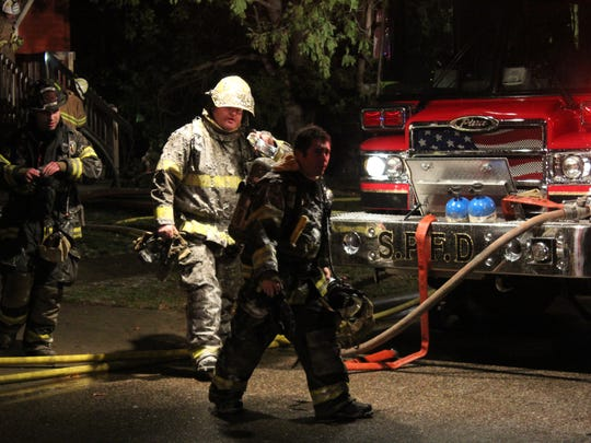 Firefighters walk out of a home after a fire Tuesday