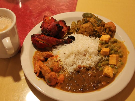 A platter of lunch buffet dishes at Cuisine India, including tandoori chicken, chicken vindaloo and dal.