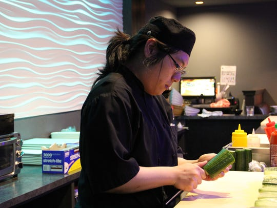 Sushi chef Allen Huang slices a cucumber for sushi