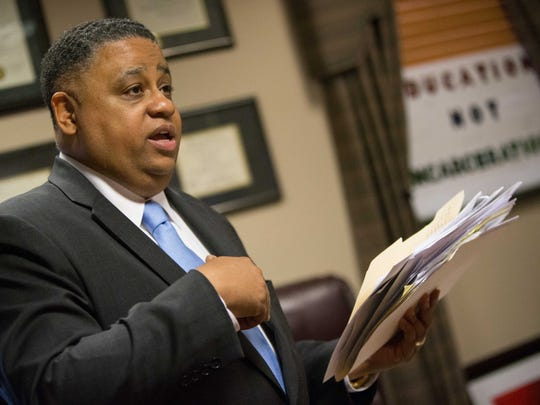 Pastor Christopher Bullock holds a stack of letters