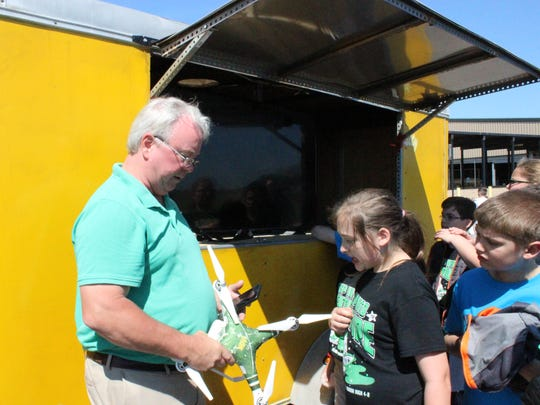 Agricultural engineer Randy Price talks with children about a drone he's about to fly during the 4-H Super Saturday event.