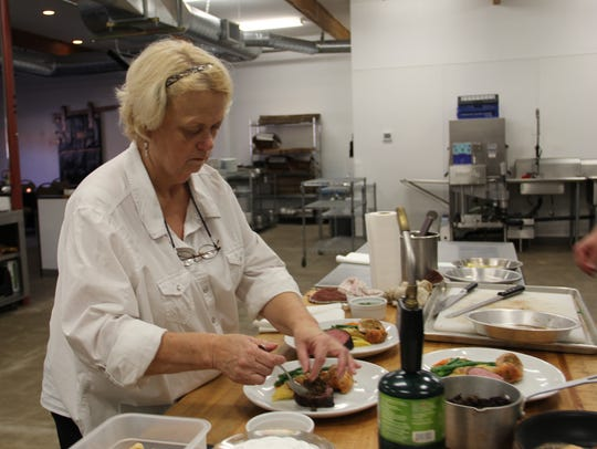 Owner Carrie Wong prepares entree plates at The Club.