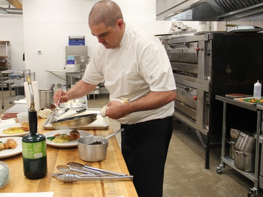 Chef Kris Spencer drizzles a sauce over entree plates at The Club.