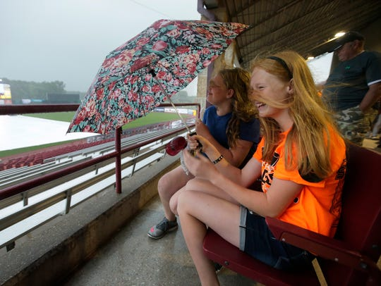 Iola-Scandinavia fans use an umbrella to protect themselves from rain and high winds during a severe weather delay before the semifinal against Laconia during the WIAA Division 3 spring baseball tournament last year at Fox Cities Stadium.