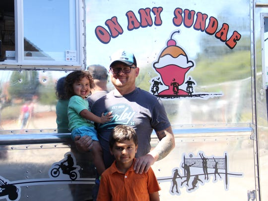 Caleb Hayward stands outside his ice cream sandwich truck, On Any Sundae, with his children Sawyer and Oliver.
