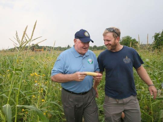 U.S. Agriculture Secretary Sonny Perdue (left) samples