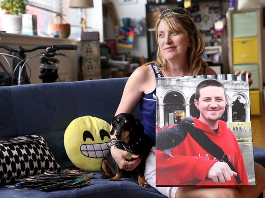 Robyn Whittaker holds a photo of her son Jordan Leavitt with his dog Rambo.