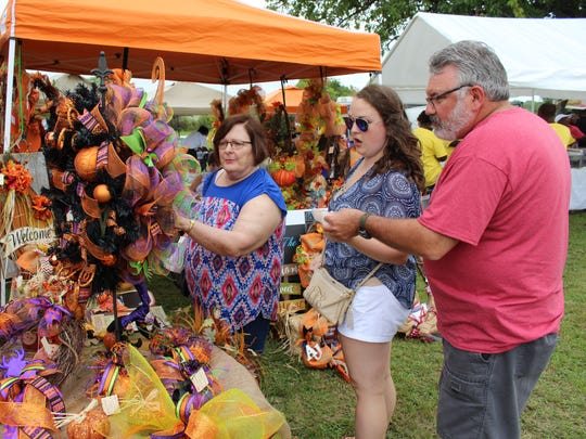 Foshee family members from left, Harriett, Amanda and Greig, examine brightly colored Halloween items at Saturday's Okra Festival. Alvin Benn/Special to the Advertiser