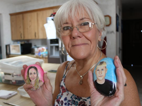 Artist Roberta Kirby holds up two of her memorial rocks: