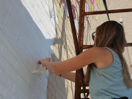 Jessica Kopecky gently peels paper off of the outline