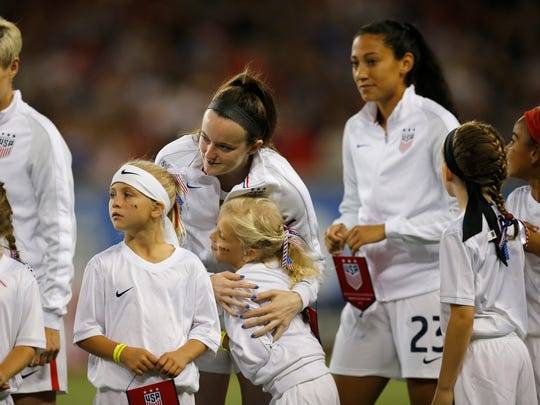 United States defender Rose Lavelle (16) hugs her escort before the first half of the international friendly match between the United States and New Zealand National Teams at Nippert Stadium in Cincinnati, on Tuesday, Sept. 19, 2017.