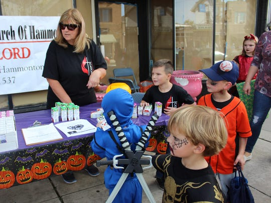 Trick-or-treaters stop by the First United Methodist Church of Hammonton's table for some refreshing juice boxes.