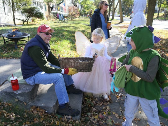 Mark Lien (left) greets trick-or-treaters Nightengale Laing-Flaaten, 6, dressed as a fairy princess, and her brother, Everett Laing-Flaaten, 8 dressed as a dragon, in front of his home on N. Downer Ave and gives them candy. In the background Lisa Lien (left) talks with Matt McGovern.  Both of Shorewood.