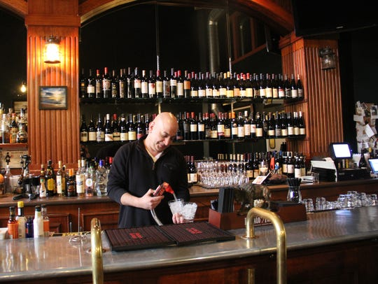 Owner Bruce Rafaei pours water at the bar of his restaurant,