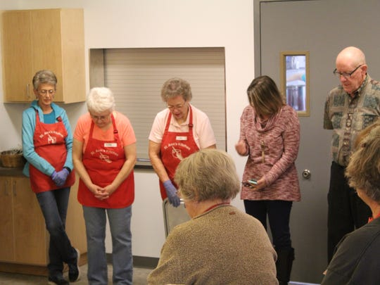 The volunteer staff at St. Ann's Kitchen pause for prayer before the kitchen's public reopening