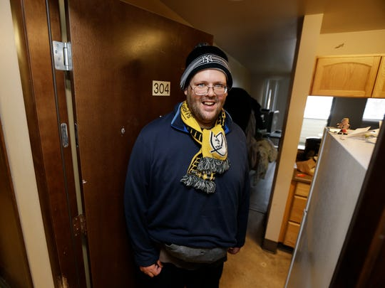 Garrick Heller stands in the doorway of his studio apartment in Everett. Heller, who was diagnosed with paranoid schizophrenia, and has lived on the streets, in shelters and eventually in a locked psychiatric facility, has been able to transition into housing and mental health counseling run by Compass Health, a Snohomish County behavioral health provider.