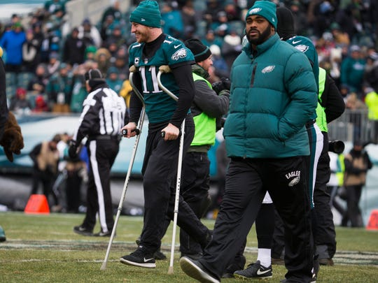Eagles quarterback Carson Wentz, 11, walks back to the sidelines on crutches after the coin toss Sunday at Lincoln Financial Field.