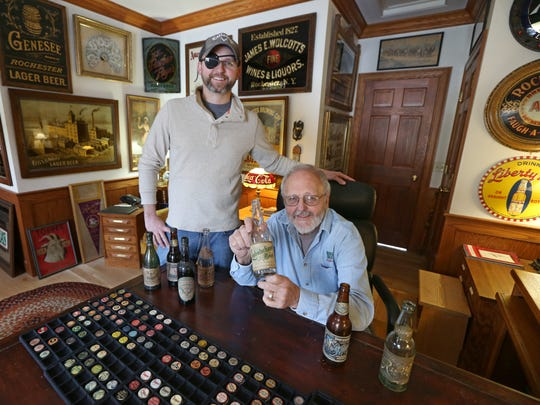 John DeVolder, seated, and son Jim DeVolder, surrounded by their collection of beer memorabilia in John's home in Ontario, Wayne County, Wednesday, Jan. 10, 2018.